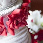 Close up of red edible flowers on a white wedding cake.