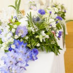Flowers on top wedding table. Blue and white flowers with greenery on a white table.