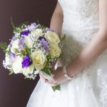 Close up of flowers held by wedding bride. Bouquet is made up of white and purple flowers.