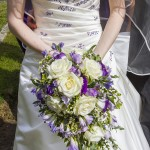 Wedding brides lower body with large bouquet of flowers. Large white roses surrounded but smaller purples and greenery