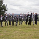 Wedding Grooms party in a line with all 12 jumping and caught mid air.