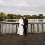 Wedding bride and groom standing in front of a fence next to of a Lake.
