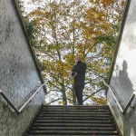 Wedding groom at the top of subway stairs in autum