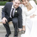 Wedding couple sitting on a park bench holding a chain on bench feet.